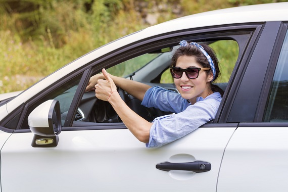 a young lady driving a car