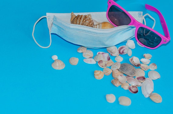 a surgical mask and sunglasses covered in sea shells