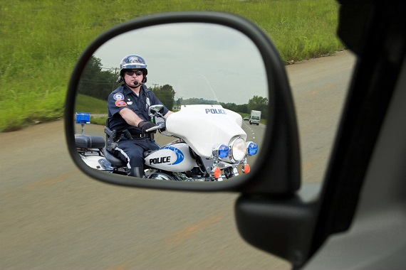 a police office on a motorcycle in a drivers side mirror