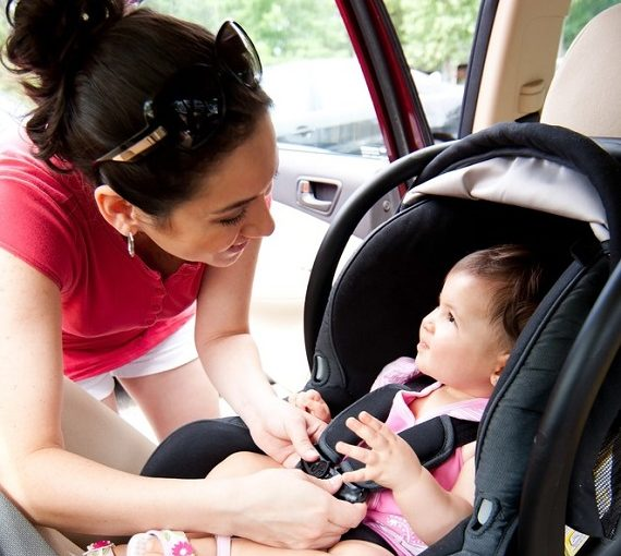 a woman buckling a baby into their car seat